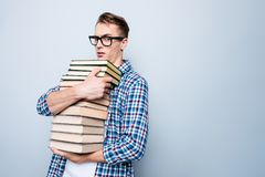 Portrait of upset, grumpy teen, teenager reader man hug pile of royalty free stock photography