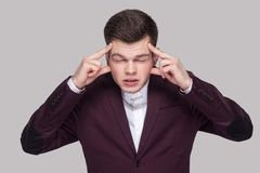 Portrait of upset handsome young man in violet suit and white sh stock photography