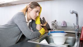 Portrait of upset young housewife in gloves looking on kitchen sink full of dirty dishes. Portrait of upset housewife in gloves looking on kitchen sink full of Stock Images