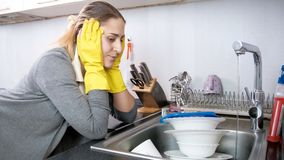Portrait of upset young housewife looking on kitchen sink with dirty dishes. Portrait of upset housewife looking on kitchen sink with dirty dishes stock photo