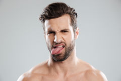 Portrait of an upset irritated naked bearded man showing tongue Stock Image