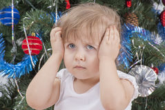 Portrait of upset little girl near the Christmas tree. Stock Photos