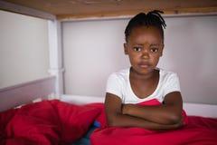 Portrait of upset little girl sitting on bed Stock Photos
