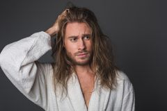 Depressed guy in white robe. Portrait of upset man holding one hand on head, looking troubled. Isolated on grey background Royalty Free Stock Images