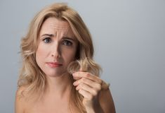 Troubled adult lady is expressing dissatisfaction of her curls. Portrait of upset middle-aged woman with damaged ends of her hair in her hand. She is looking at Royalty Free Stock Images