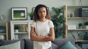 Portrait of upset and offended African American lady standing at home with arms crossed making angry face frowning and stock video footage