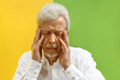 Portrait of upset old man rubbing his eye while crying. Portrait of upset old man covering face while crying. Isolated on color background stock images