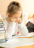 Portrait of upset schoolgirl looking at textbook with homework Royalty Free Stock Images