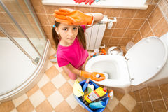 Portrait of upset tired girl cleaning toilet with brush Stock Photos
