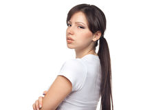 Portrait of upset woman against white background. Angry young woman with crossed arms on white background Stock Image