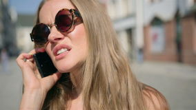 Portrait of upset woman talking on phone  in a city street. Closeup portrait of upset sad, angry, unhappy, serious woman wearing retro round sunglasses talking stock footage