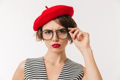 Portrait of an upset woman wearing red beret. And eyeglasses looking at camera isolated over white background Royalty Free Stock Image