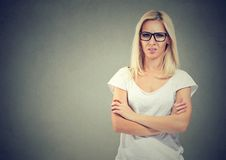 Upset young casual woman standing with arms folded stock photo