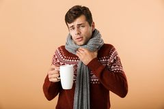 Portrait of an upset young man dressed in sweater. And scarf holding cup with tea isolated over beige background stock photos