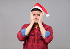 Portrait of upset young man in red santa claus hat Stock Photography