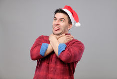 Portrait of upset young man in red santa claus hat Stock Images