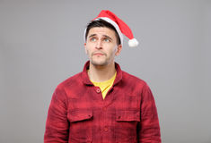 Portrait of upset young man in red santa claus hat Stock Photos