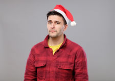 Portrait of upset young man in red santa claus hat Royalty Free Stock Photos