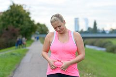 Upset young woman looking at her belly fat. Portrait of an upset young woman looking annoyed at her belly fat while wearing fitness pink sleeveless top outdoors Royalty Free Stock Photography