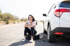 Woman looking upset with flat tyre on her car. Portrait of upset young woman sitting on spare tyre on road while changing the flat wheel of her car Royalty Free Stock Photography