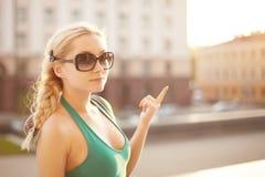 Portrait urbain de fille blonde modèle heureuse élégante dans la robe et des lunettes de soleil vertes avec des cheveux tressés d images libres de droits