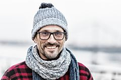 Portrait of happy urban man in winter knitted wear. Portrait of man in glasses and knitted white-blue scarf and hat. Portrait of urban men in winter knitted stock photography