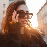 Portrait of an urban stylish woman hipster in trendy sunglasses in a stylish black coat on the background of bright orange sun. Highlights. Luxurious beautiful royalty free stock photography