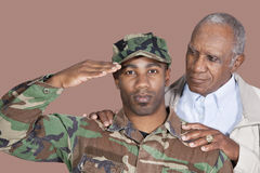 Portrait of US Marine Corps soldier with father saluting over brown background stock image