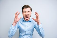 Portrait of very angry, annoyed, wild man shouting, yelling, holding hands near face, standing over grey background royalty free stock images