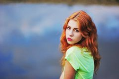 Portrait of a very beautiful brown eyed girls with bright red hair in  light green dress on  background  lake. Portrait of a very beautiful brown eyed girls with Royalty Free Stock Photos
