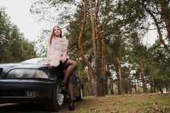 Portrait of a very beautiful girl in a forest dressed in fur in a car Royalty Free Stock Photography
