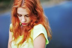 Portrait of a very beautiful girl with long red hair lowered gaz. E in a light-green t-shirt on the background of the water on a summer day Royalty Free Stock Photo