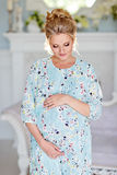 The portrait is very beautiful, mile, feminine and tender pregnant girl blonde in blue dress with floral print against a light in. Terior, with your eyes closed stock images