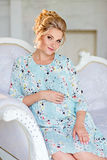The portrait is very beautiful, mile, feminine and tender pregnant girl blonde in a blue dress with a floral print, sitting on th. E couch on a background of stock image