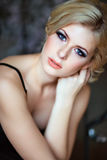 Portrait of a very beautiful sensual girls blonde with smoky ice. In a black dress, close-up Royalty Free Stock Photo