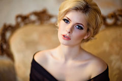 Portrait of a very beautiful sensual girls blonde with smoky ice. In a black dress, in the interior, close-up Royalty Free Stock Photo