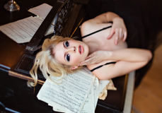 Portrait of a very beautiful sensual girls blonde with smoky ice. In a black dress lying on a black piano in the interiors of old house Royalty Free Stock Photo