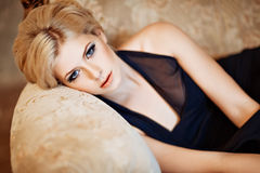 Portrait of a very beautiful sensual girls blonde with smoky ice. In a black dress lying on the sofa in the interior, close-up Royalty Free Stock Photo