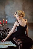 Portrait of a very beautiful sensual girls blonde with smoky ice. In a black dress sitting on a black piano in the interiors of old houses Stock Photo