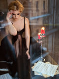 Portrait of a very beautiful sensual girls blonde with smoky ice. In a black dress sitting on a black piano in the interiors of old house Stock Photography