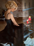 Portrait of a very beautiful sensual girls blonde with smoky ice. In a black dress sitting on a black piano, in profile, in the interiors of old house Royalty Free Stock Image