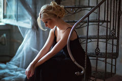 Portrait of a very beautiful sensual girls blonde with smoky ice. In a black dress, sitting on a metal ladder in profile Stock Image