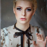 Portrait of a very beautiful sensual girls blonde with smoky ice. In black-and-white blouse with bow, looking through the window, a sad look Stock Photo