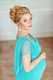 Portrait of a very beautiful, sweet, feminine and tender pregnant blonde girl with green eyes in a blue dress with rhinestones on. A background of bright stock photos