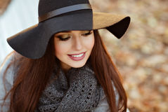 Portrait of a very beautiful young brunette woman with shiny straight hair in a gray coat and black hat smiling with downcast eye royalty free stock image