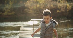 Portrait of a very charismatic boy three years old standing on the bridge beside the lake and looking straight to the stock video