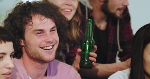 Portrait of a very charismatic guy with curly hair and speckle watching excited and concentrated a football match in. Front of TV whit his big company of stock footage