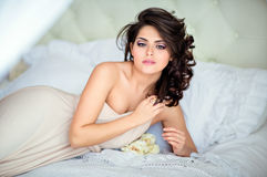 Portrait of a very gentle sensual girls brunette lying on a whit. E bed in a beige dress Stock Photo