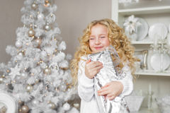 Portrait of very glad little girl with a gift box at hands in a light new year decoration studio Stock Image