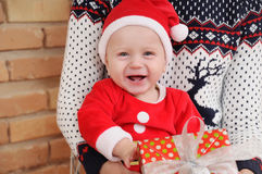Portrait of very happy cute little baby boy in Santa suit with g Royalty Free Stock Photo
